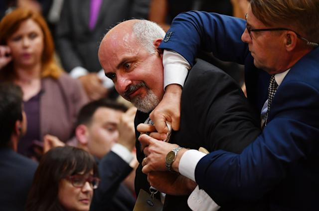 "<span class=""s1"">Sam Husseini is escorted out of the press conference room at the Presidential Palace in Helsinki. (Photo: Yuri Kadobnov/AFP/Getty Images)</span>"