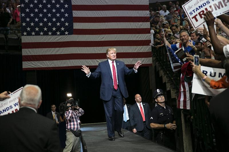US Republican presidential candidate Donald Trump greets supporters during a campaign rally at the American Airlines Center in Dallas on September 14, 2015