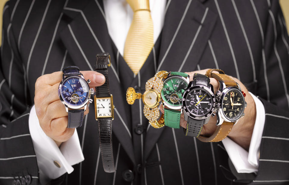 Close up of a black market trader's hands with a collection of watches.