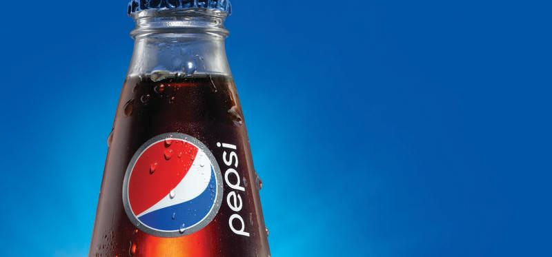 A glass Pepsi bottle over blue background.