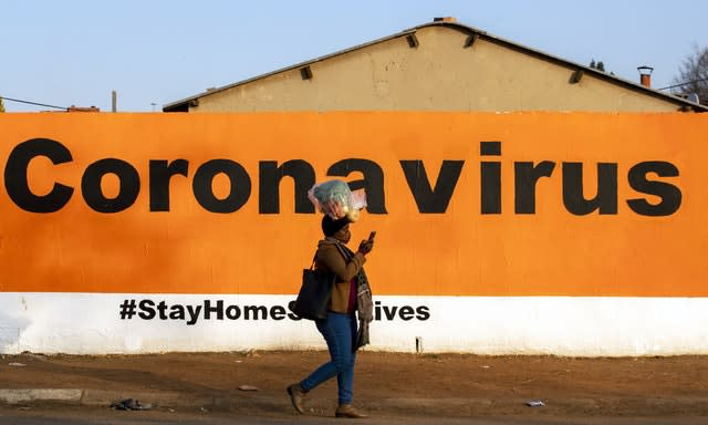 A woman wearing a face mask passes a coronavirus sign (Themba Hadebe/AP)