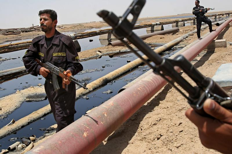 FILE - In this June 22, 2008 file photo, Iraqi police officers protecting oil installations secure an oil pipeline from the Rumailah refinery, north of Basra, Iraq. A senior Iraqi official on Wednesday said his country expects to ramp up oil production to 4.5 million barrels per day by the end of next year from around 3.5 million barrels now, thanks to work by a handful of international oil companies developing the country's prized oil and gas fields. (AP Photo/Nabil al-Jurani, File)