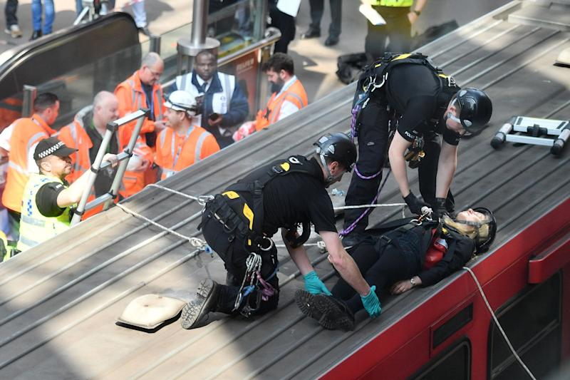 Police remove a woman from the roof of a DLR train at Canary wharf (AFP/Getty Images)