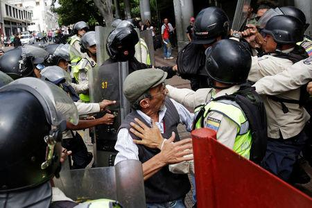 Pro-government supporters clash with riot police as opposition supporters protest against Venezuelan President Nicolas Maduro's government outside the courthouse in Caracas