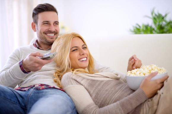 A smiling young couple, leaning on each other and a couch with popcorn and a TV remote close at hand.