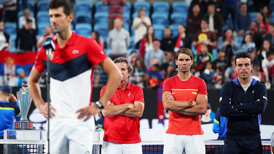 Rafael Nadal, pictured here watching on as Novak Djokovic delivers his victory speech.