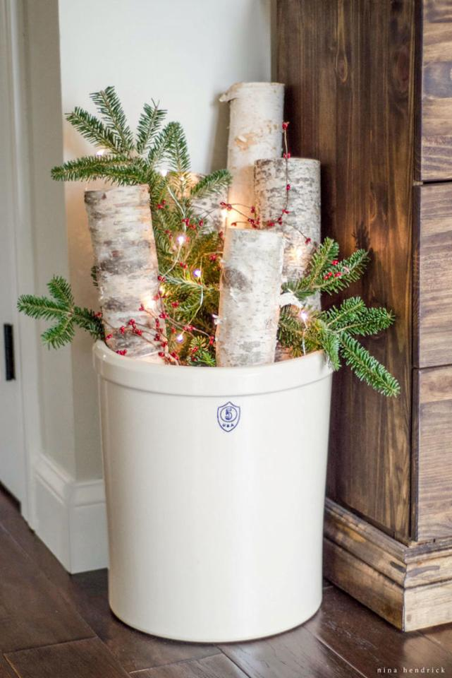 """<p>This bundle of birch logs, berries, and Christmas tree clippings will look perfect in the foyer. Add a string of lights for extra sparkle. </p><p><strong>See more at <a rel=""""nofollow"""" href=""""http://www.ninahendrick.com/christmas-home-tour-2015-part-2/"""">Nina Hendrick</a>.</strong></p>"""
