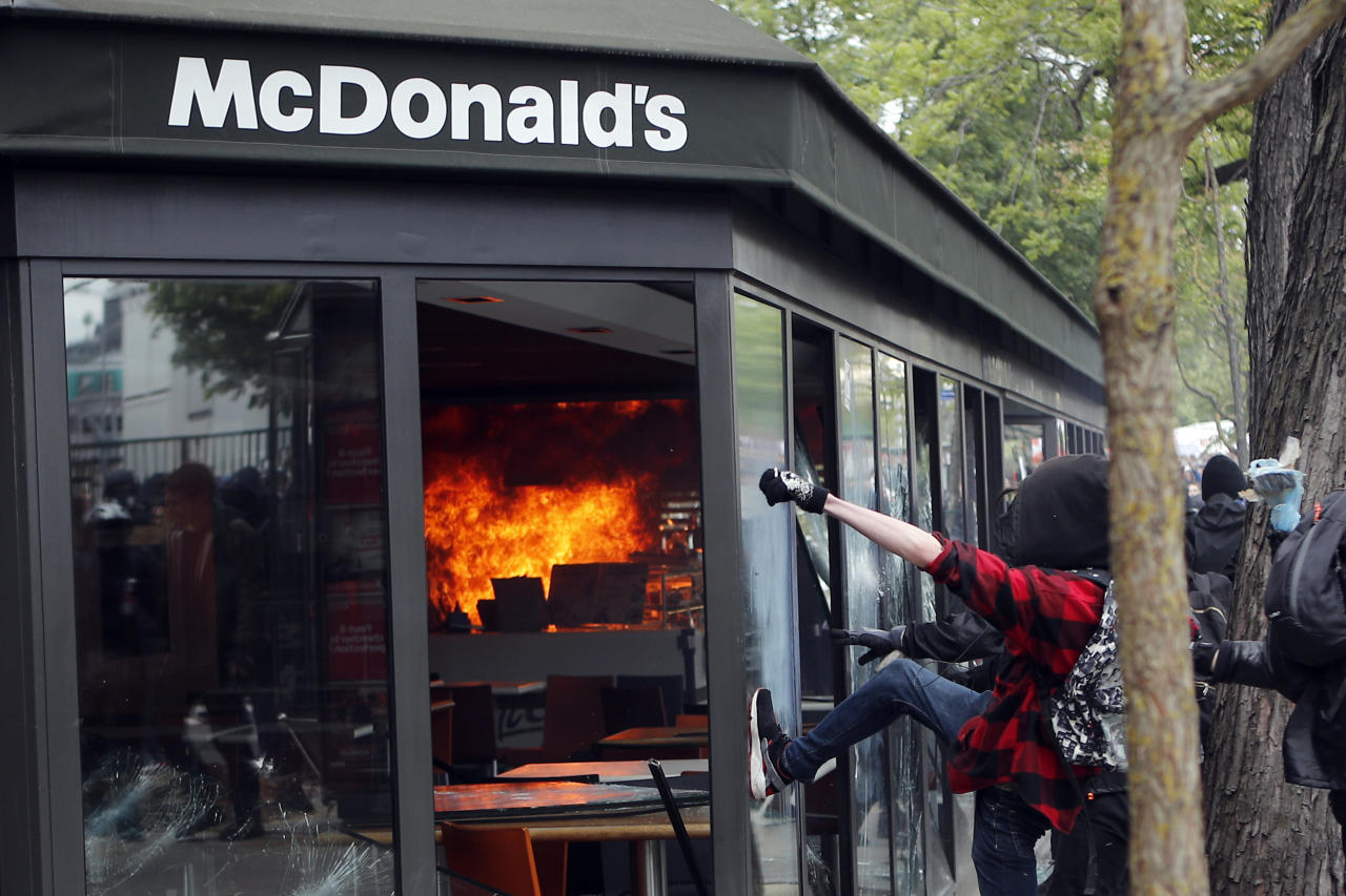 <p>A McDonald's restaurant is hit with petrol bombs thrown by activists during the traditional May Day rally in the center of Paris, France, May 1, 2018. Each year, people around the world take to the streets to mark International Workers' Day, or May Day. (Photo: Francois Mori/AP) </p>