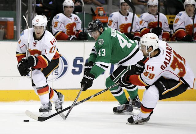 Dallas Stars right wing Valeri Nichushkin (43), of Russia, competes against Calgary Flames center Mikael Backlund (11), of Sweden, and T.J. Galiardi (39) for control of the puck in the second period of an NHL hockey game on Thursday, Oct. 24, 2013, in Dallas. (AP Photo/Tony Gutierrez)