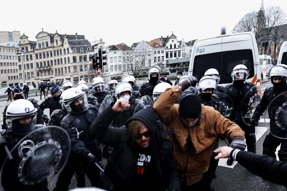 Belgian Police officers push back demonstrators during an unauthorized demonstration against measures taken in order to stem the spread of the Covid-19 pandemic near the Brussels Central Station, in Brussels, on January 31, 2021. (Photo by Kenzo TRIBOUILLARD / AFP) (Photo by KENZO TRIBOUILLARD/AFP via Getty Images) (Photo: KENZO TRIBOUILLARD via Getty Images)