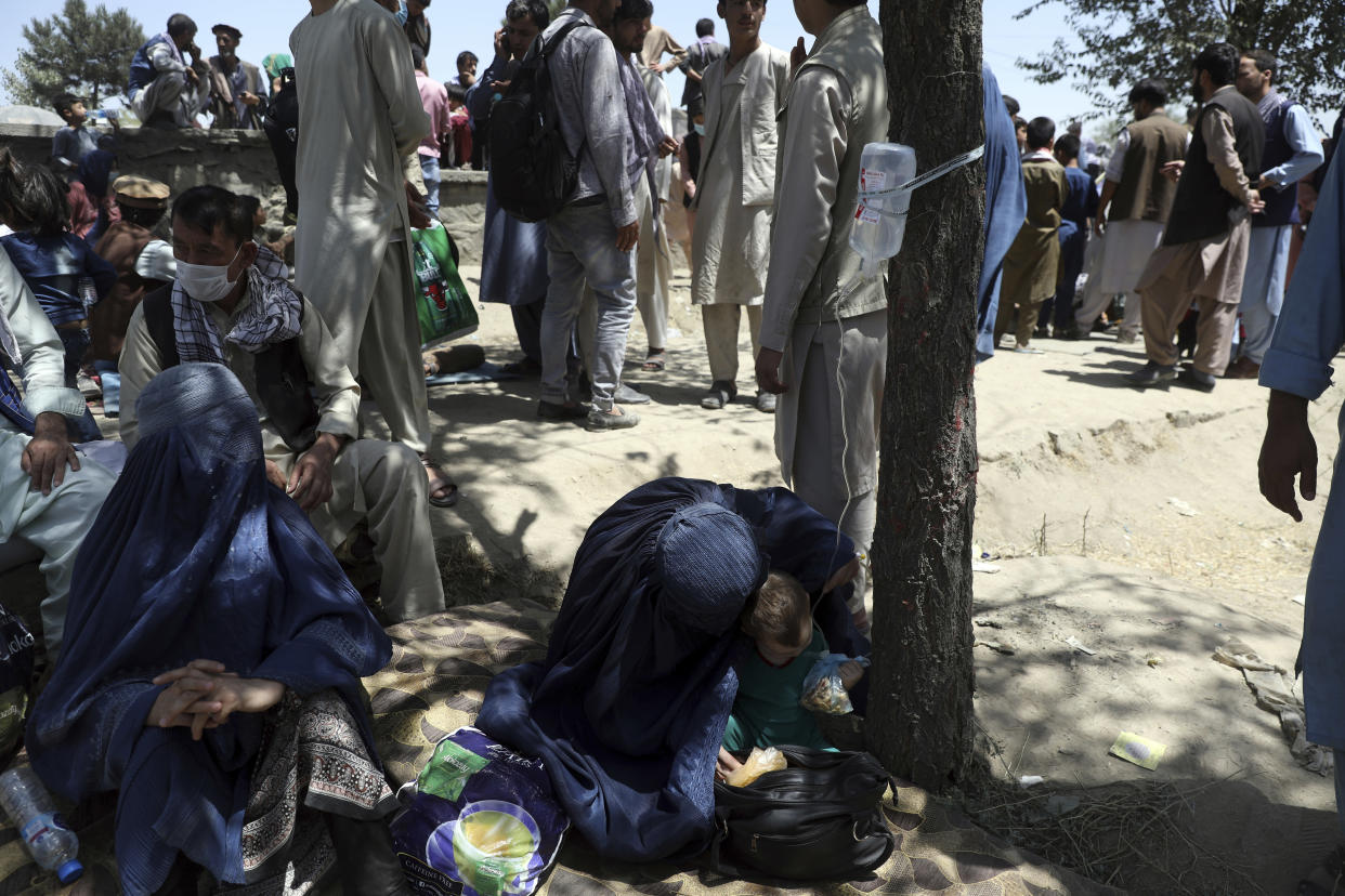 Internally displaced Afghan women from northern provinces, who fled their home due to fighting between the Taliban and Afghan security personnel, receive medical care in a public park in Kabul, Afghanistan, Tuesday, Aug. 10, 2021. (AP Photo/Rahmat Gul)