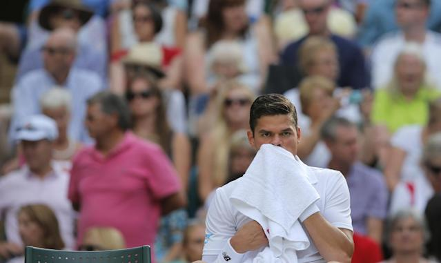 Milos Raonic of Canada sits in his chair and wipes his face during a game break as he plays against Roger Federer of Switzerland during their men's singles semifinal match at the All England Lawn Tennis Championships in Wimbledon, London, Friday, July 4, 2014. (AP Photo/Pavel Golovkin)