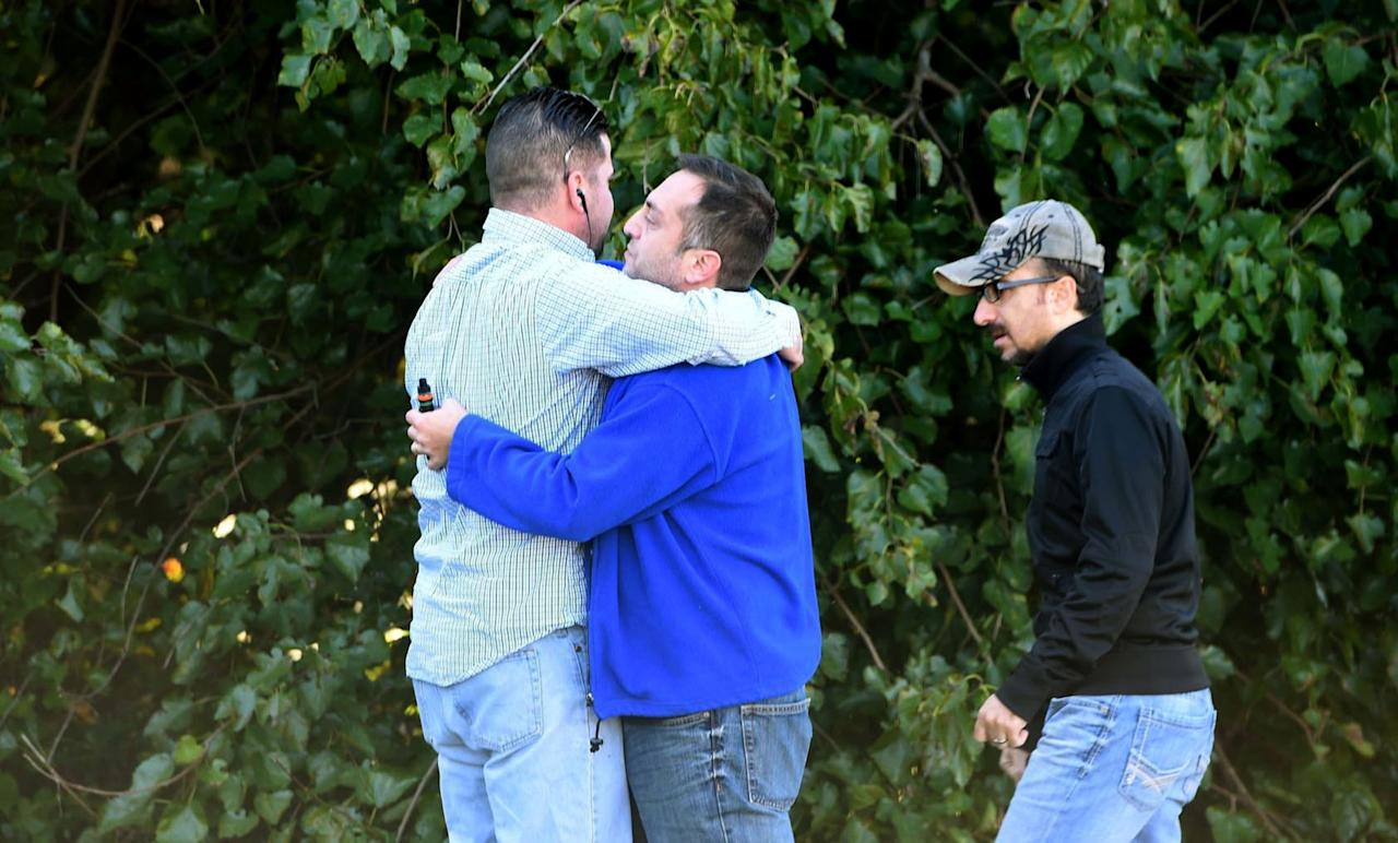 <p>Unidentified bystanders embrace as police and Emergency Medical Services respond to a shooting at a business park in the Edgewood area of Harford County, Md., Wednesday, Oct. 8, 2017. (Photo: Matt Button/The Baltimore Sun via AP) </p>