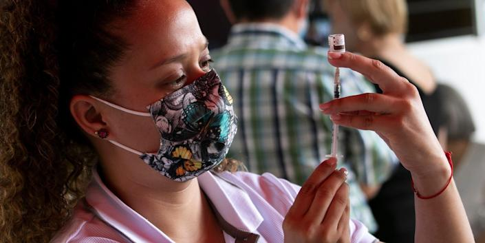 A nurse wearing a flowered mask and a pink shirt measures out a dose of COVID-19 vaccine on May 7, 2021 in Escazu, Costa Rica, as two people are blurry in the background