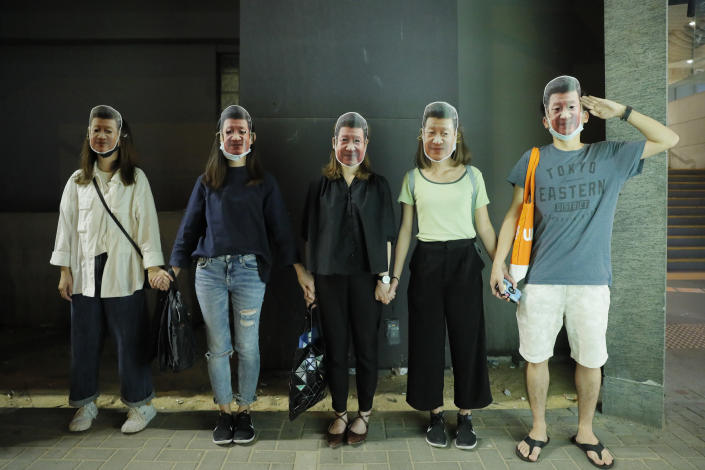 Protesters wear masks of Chinese President Xi Jinping in Hong Kong, Friday, Oct. 18, 2019. Hong Kong pro-democracy protesters are donning cartoon/superhero masks as they formed a human chain across the semiautonomous Chinese city, in defiance of a government ban on face coverings. (AP Photo/Kin Cheung)