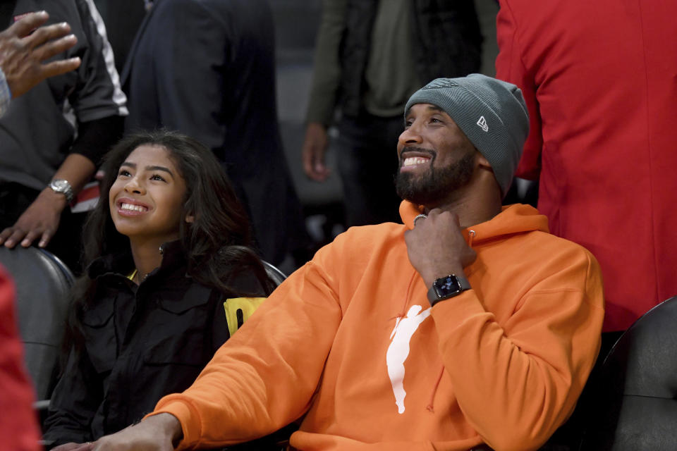 Kobe Bryant in an orange sweatshirt with the WNBA logo and his daughter, Gianna.