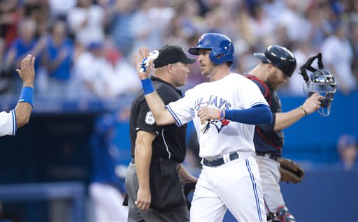 Toronto Blue Jays catcher J.P. Arencibia celebrates scoring as Minnesota Twins catcher Ryan Doumit reacts during the fourth inning of a baseball game in Toronto on Friday, July 5, 2013. (AP Photo/The Canadian Press, Frank Gunn)