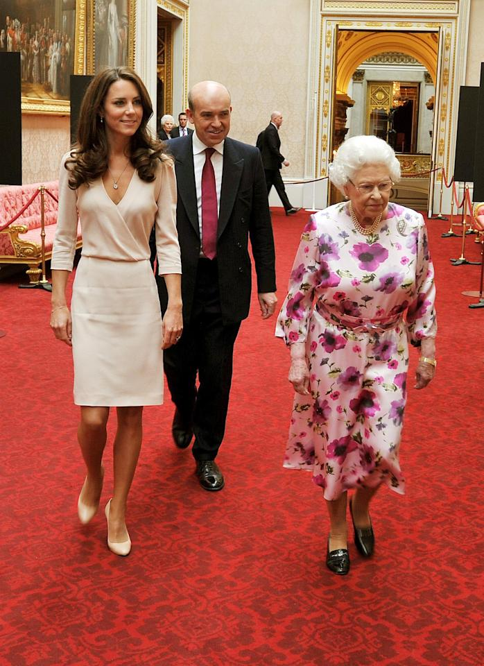 <p>Kate and the Queen view an exhibition of her wedding dress at Buckingham Palace.<em> [Photo: PA]</em> </p>