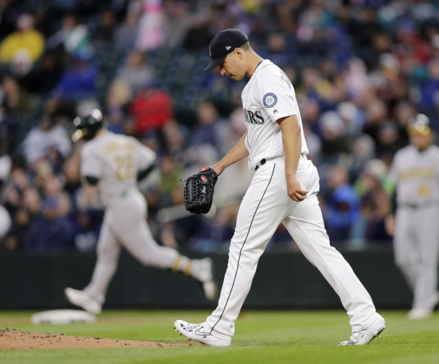 Seattle Mariners starting pitcher Marco Gonzales walks to the mound with Oakland Athletics' Ramon Laureano rounding the bases behind after hitting a solo home run during the third inning of a baseball game, Saturday, Sept. 28, 2019, in Seattle. (AP Photo/John Froschauer)