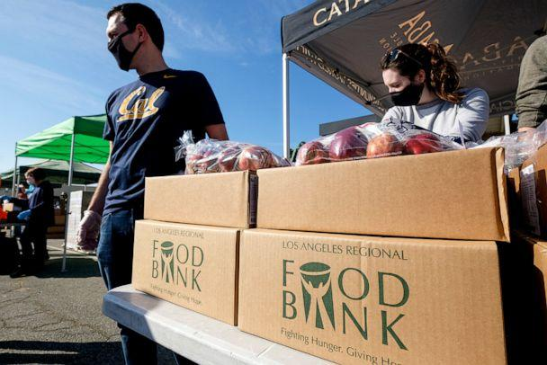 PHOTO: Volunteers wait to load food into the trunk of vehicles during a ''Let's Feed L.A. County'' food distribution in Burbank, Calif., Nov. 14, 2020. (Ringo Chiu/Zuma Press)