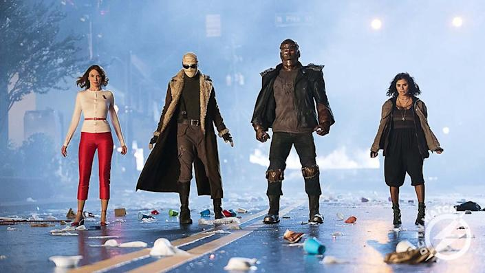 A still from the first season of Doom Patrol shows Rita Farr, Negative Man, Robot Man, and Crazy Jane standing on a road looking shocked