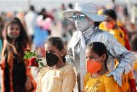 People pose with a performance artist at a beach amidst the spread of the coronavirus disease (COVID-19) in Mumbai