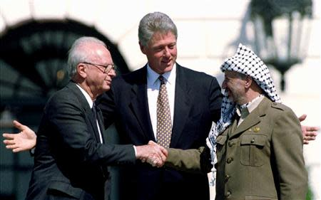File picture of U.S. President Clinton gesturing as Israeli PM Rabin and PLO Chairman Arafat shake hands after signing the Israeli-PLO peace accord
