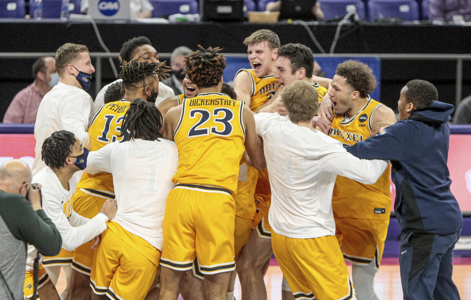 Drexel players celebrate after defeating Elon during an NCAA college basketball game for the Colonial Athletic Association men's tournament championship in Harrisonburg, Va., Tuesday, March 9, 2021. (AP Photo/Daniel Lin)