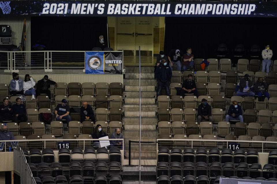 A limited amount of fans attend a game between Villanova and Winthrop in the second half of a first round game in the NCAA men's college basketball tournament at Farmers Coliseum in Indianapolis, Saturday, March 20, 2021. Villanova defeated Winthrop 73-63. Restrictions due to the COVID-19 pandemic have limited crowds, reduced interactions and created an abnormal NCAA experience for those involved. It's sacrifices they've all been asked to make by the NCAA to pull off a tournament in the midst of the ongoing pandemic. (AP Photo/Michael Conroy)