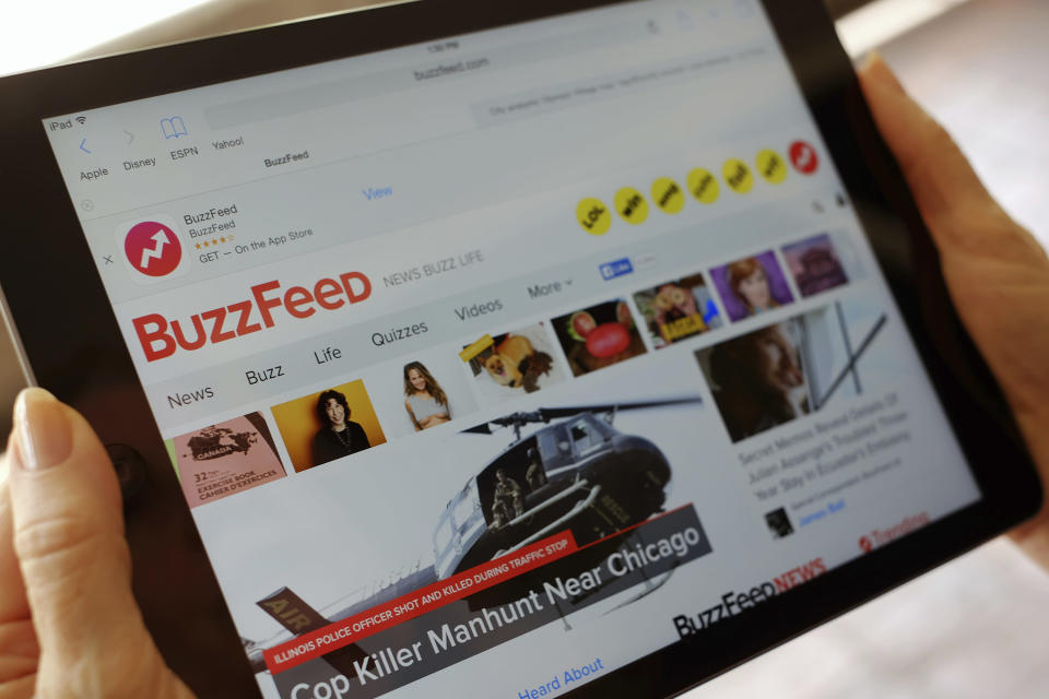 FILE- In this Sept. 2, 2015, file photo the BuzzFeed website is displayed on an iPad held by an Associated Press staffer in Los Angeles. BuzzFeed is buying HuffPost from Verizon as part of a bigger deal that has the wireless giant investing in the digital-media company. (AP Photo/Richard Vogel, File)