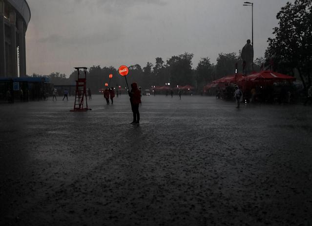 Volunteers are seen during heavy rain outside Luzhniki stadium after the World Cup final soccer match in Moscow, Russia July 15, 2018. As well as shooting all the matches, Reuters photographers are producing pictures showing their own quirky view from the sidelines of the World Cup. REUTERS/Gleb Garanich