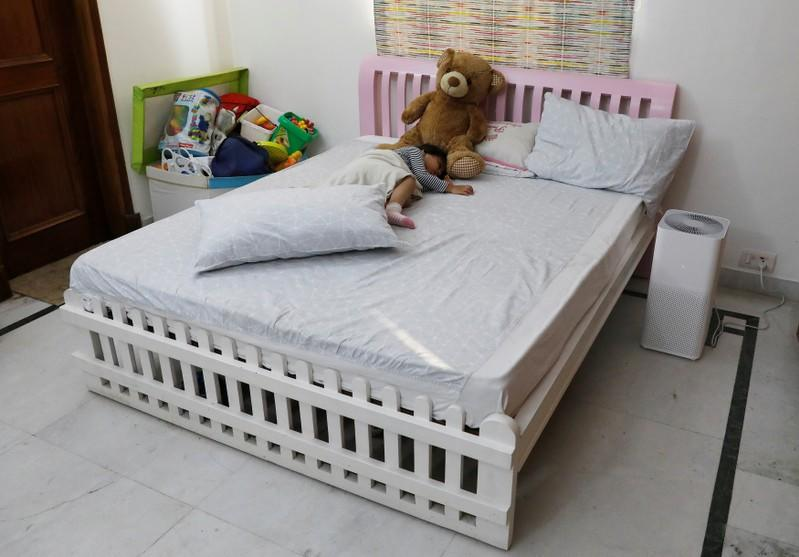 Mehreen, 3, daughter of Nabeela Moinuddin sleeps next to an air purifier inside her room at her house in New Delhi