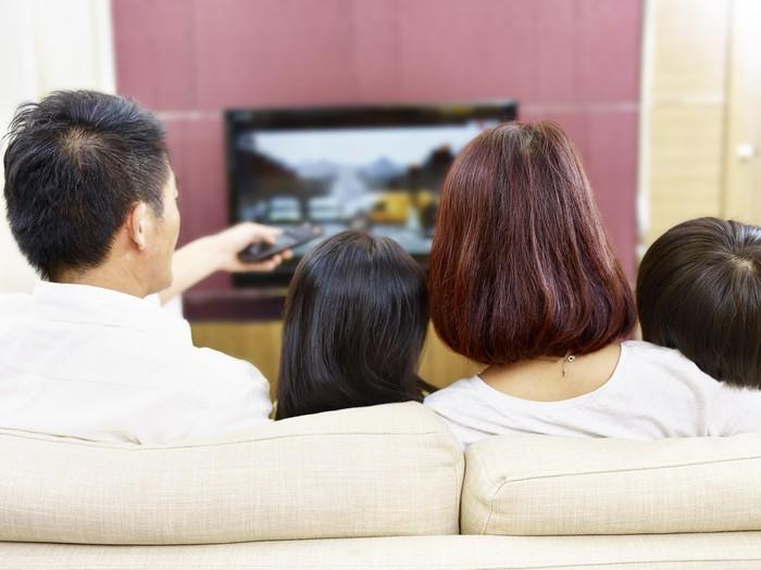 Family sitting on the couch and watching television