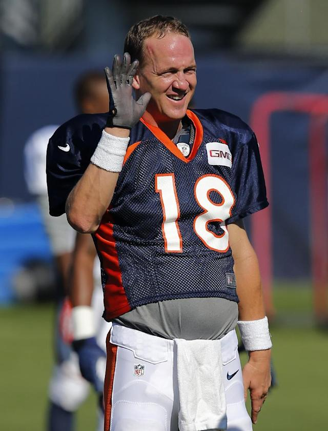 FILE - In this Aug. 12, 2014, file photo, Denver Broncos' Peyton Manning holds up his gloved throwing hand during NFL football training camp in Englewood, Colo. (AP Photo/Jack Dempsey, File)