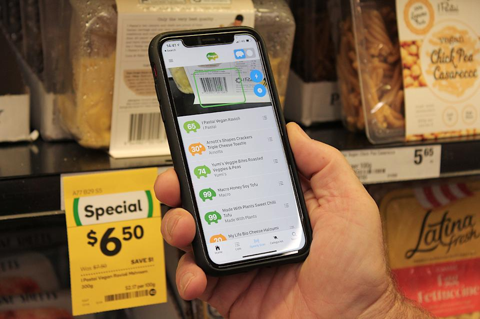 A phone using the Strayan app scans a product in Woolworths.