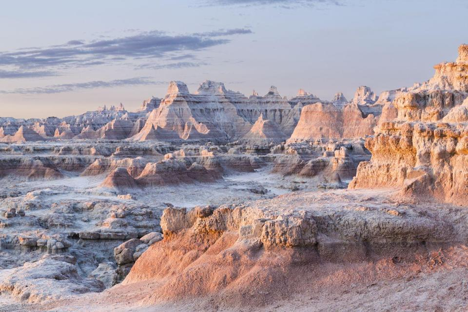 """<p><a href=""""https://www.nps.gov/badl/index.htm"""" rel=""""nofollow noopener"""" target=""""_blank"""" data-ylk=""""slk:Badlands National Park"""" class=""""link rapid-noclick-resp""""><strong>Badlands National Park </strong></a></p><p>If you are in South Dakota, you are probably going to go see Mount Rushmore, and you should. It is an amazing landmark. But while you are in the state, you should also make time to visit Badlands. This expansive park has rock formations that make you feel like you are in the Grand Canyon, alongside some amazingly colorful hills, desert touches, and beautiful prairie land. A daylong drive through this park will make you feel like you've seen four parks in one. </p>"""