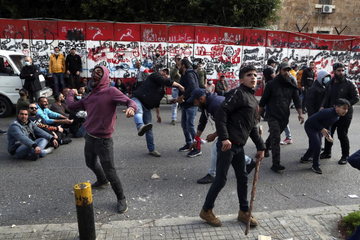 Protesters throw stones towards the central bank building, during a protest in Beirut, Lebanon, Saturday, March. 13, 2021. Riot police fired tear gas to disperse scores of people who protested near parliament building in central Beirut Saturday amid deteriorating economic and financial conditions and as the local currency hit new low levels. (AP Photo/Bilal Hussein)