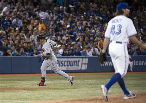 Cleveland Indians shortstop Asdrubal Cabrera, left, rounds the bases past Toronto Blue Jays R.A. Dickey, right, after hitting a two-run home run during fifth inning of an opening day baseball game in Toronto on Tuesday, April 2, 2013. (AP Photo/The Canadian Press, Nathan Denette)