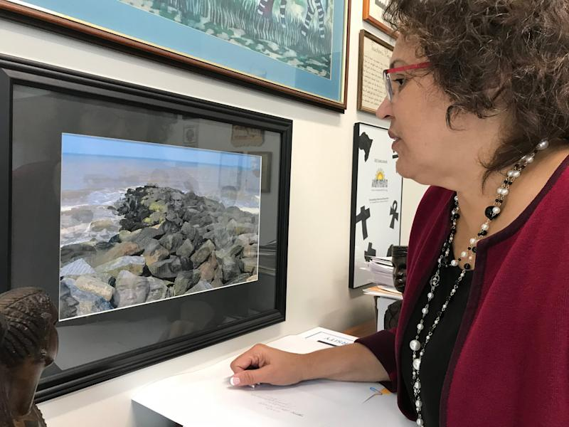 """Cassandra Newby-Alexander, history professor and dean of Norfolk State University's College of Liberal Arts looks at a photograph entitled """"The Ancestors"""" by Elvira Welbeck inside her office on Friday, Nov. 22, 2019 in Norfolk, Virginia."""