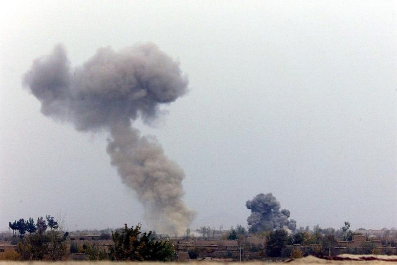 Smoke billows in the distance in Rabat as US fighter jets bomb the Taliban frontline 22 October 2001, some 50 kilometers (some 35 miles) from Kabul, in the Parwan province. Afghan officials on Sept 10 2014 allege US airtrikes kill 11 civilians (AFP Photo/Jack Guez)