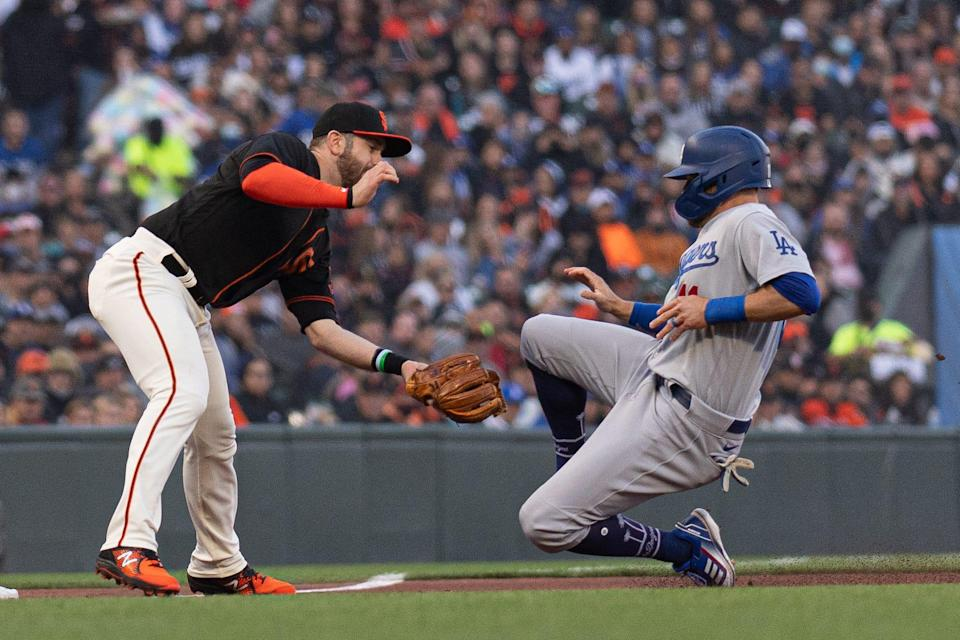 San Francisco Giants third baseman Evan Longoria (10) tags out Los Angeles Dodgers left fielder AJ Pollock (11) during the first inning at Oracle Park during a regular-season game.