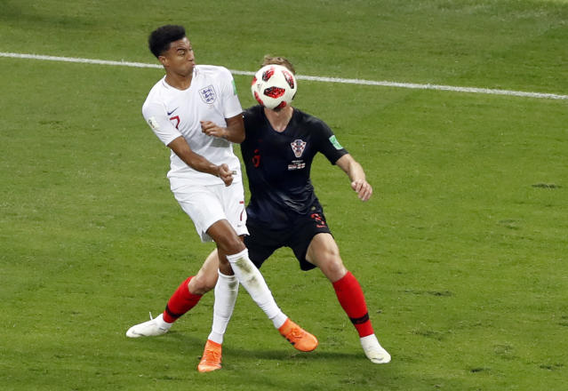England's Jesse Lingard, left, duels for the ball with Croatia's Ivan Strinic during the semifinal match between Croatia and England at the 2018 soccer World Cup in the Luzhniki Stadium in Moscow, Russia, Wednesday, July 11, 2018. (AP Photo/Darko Bandic)