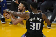 Golden State Warriors guard Stephen Curry, left, is defended by Sacramento Kings forward Glenn Robinson III during the first half of an NBA basketball game in San Francisco, Monday, Jan. 4, 2021. (AP Photo/Jeff Chiu)