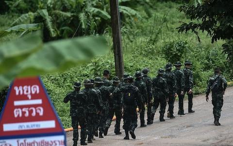 <span>Thai soldiers walk into to the Tham Luang cave complex on Tuesday morning</span> <span>Credit: YE AUNG THU /AFP </span>