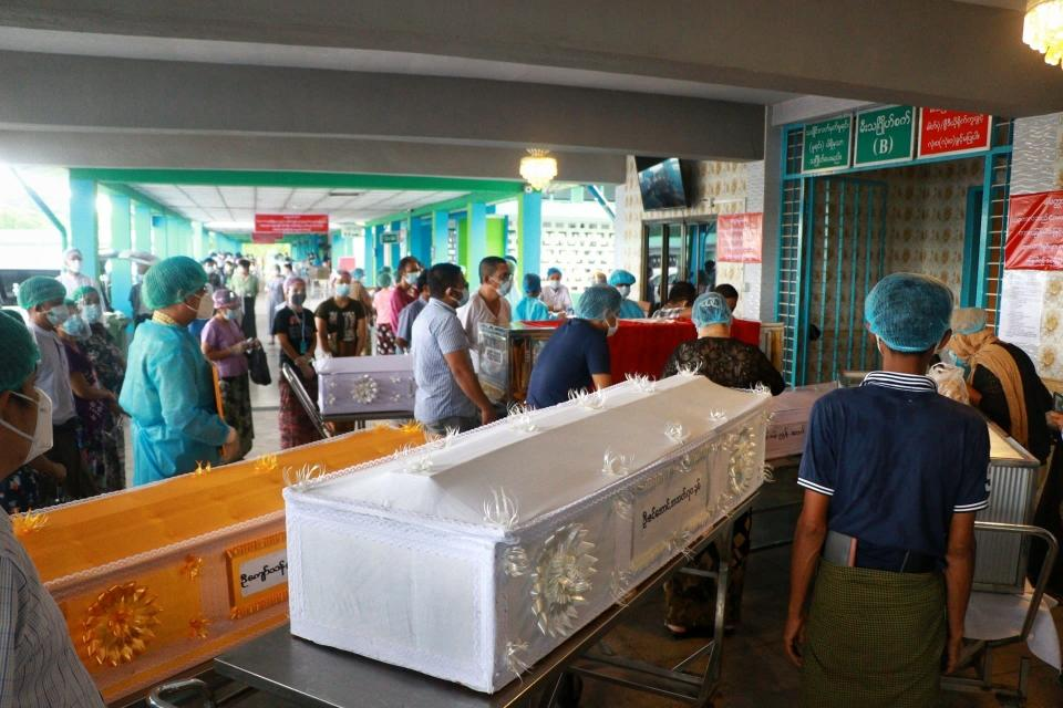 People wearing face masks wait while caskets with bodies are queued outside a crematorium at the Yay Way cemetery in Yangon, Myanmar, Wednesday July 14, 2021. The number of people dying in Myanmar's biggest city, Yangon, which is facing a coronavirus surge and a shortage of oxygen to treat patients, has been climbing so quickly that charity groups said Wednesday they are almost overwhelmed. (AP Photo)
