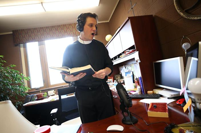 "<span class=""caption"">The Rev. Philip Dinwiddie sings to a pre-recording of mass at St. James Episcopal Church in Grosse Ile, Michigan.</span> <span class=""attribution""><a class=""link rapid-noclick-resp"" href=""https://www.gettyimages.com/detail/news-photo/the-rev-philip-dinwiddie-sings-in-his-office-adding-music-news-photo/1220888445?adppopup=true"" rel=""nofollow noopener"" target=""_blank"" data-ylk=""slk:Gregory Shamus/Getty Images"">Gregory Shamus/Getty Images</a></span>"
