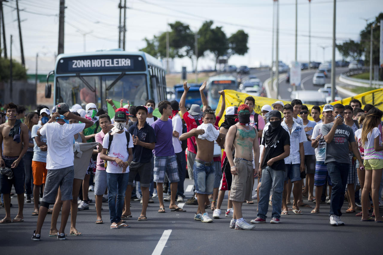 Protestors block the main road leading to the Castelao stadium before the start of a soccer Confederations Cup group B match between Nigeria and Spain in Fortaleza, Brazil, Sunday, June 23, 2013. Small gatherings occurred Sunday in a few cities, no clashes were reported. On Saturday a quarter-million Brazilians protested in more than 100 cities, but the gatherings were less violent than those seen earlier in the week. (AP Photo/Victor R. Caivano)