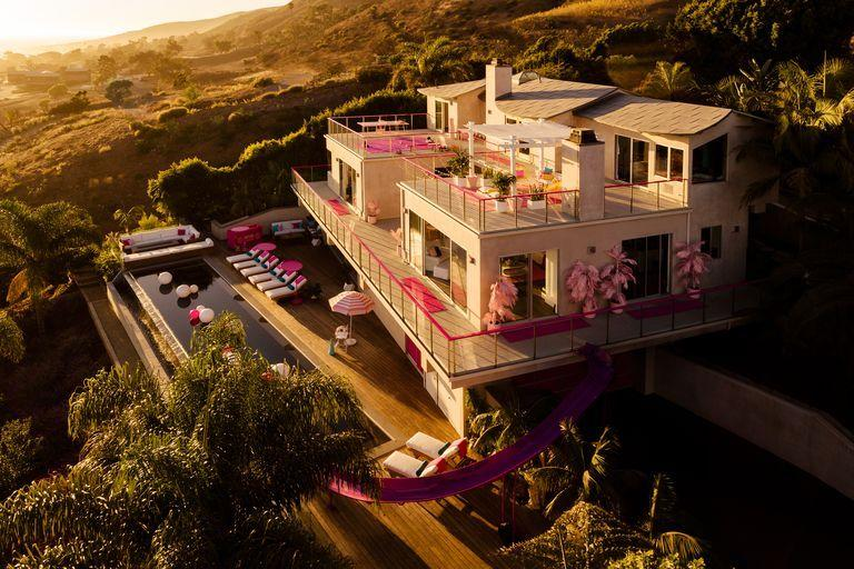 """<p>A truly historic, childhood-dream event is happening on October 23 at 2 P.M. ET/11 A.M. PT: Barbie's Malibu dream house—a real place that exists in California, at least for the time being—will be available to rent on Airbnb for the first time...and only time ever, allegedly. </p><p>Barbie's listing is already up <a href=""""https://www.airbnb.com/rooms/38933153"""" target=""""_blank"""">here</a>, and Airbnb released some truly incredible photos of the property. One lucky guest will be able to reserve the entire house for $60 a night (in honor of Barbie's 60th anniversary) and spend two nights on the property: Sunday, October 27 to Tuesday, October 29, with up to three friends.</p><p>In the words of Barbie on her Airbnb listing: """"I promise the memories will last a lifetime,"""" and also """"this is a once in a lifetime chance."""" How bittersweet for most of us.</p><p>Features include an infinity pool with views of the beach, a personal cinema, a hobby studio, a sport court, a meditation space, an outdoor dining patio, and a fully-stocked kitchen. The house has a ton of life-size Barbie accessories and splashes of pink in practically every room. </p><p>There's some additional perks too for the lucky renter because staying in Barbie's dream house is a full-fledge Airbnb experience. The guests staying on October 27 to 29 will have a meet-and-greet with hairstylist Jen Atkin, a one-on-one fencing lesson with fencing medalist Ibtihaj Muhammad, a globally-inspired cooking lesson with Gina Clarke-Helm of Malibu Seaside Chef, and a behind-the-scenes tour of Columbia Memorial Space Center with pilot and aerospace engineer Jill Meyers. </p>"""