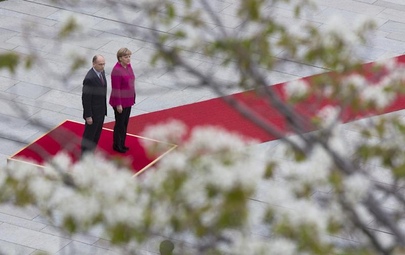 Seen through a tree in blossom, German Chancellor Angela Merkel, right, welcomes Italian Prime Minister Enrico Letta, left, with military honors at the chancellery in Berlin, Germany, Tuesday, April 30, 2013. (AP Photo/Gero Breloer)