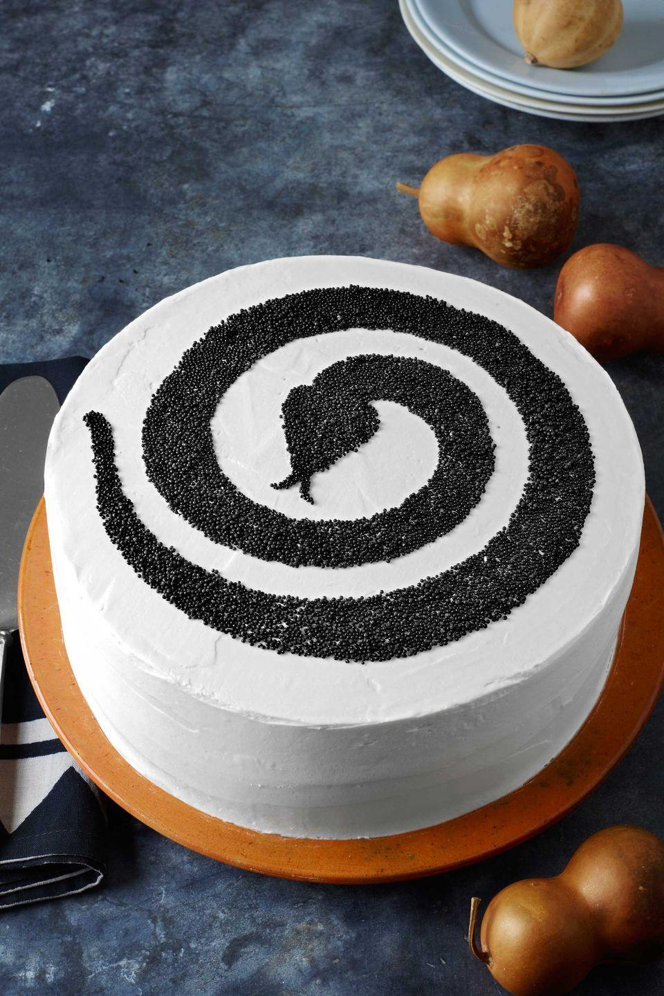 """<p>Give a round cake real bite with our <a href=""""http://clv.h-cdn.co/assets/cm/15/24/5578bab00b517_-_1013-snakecakeart.pdf"""" rel=""""nofollow noopener"""" target=""""_blank"""" data-ylk=""""slk:snake template"""" class=""""link rapid-noclick-resp"""">snake template</a> and black nonpareils<em>. </em></p><p><strong>Step 1: </strong>Prepare your favorite cake recipe and bake in two 9-inch round cake pans. Let the cakes cool completely.<br></p><p><strong>Step 2: </strong>Cut the tops off each cake and frost one of the tops with store bought or homemade buttercream. Place bare cake on top of the frosted top. Frost both cakes together.</p><p><strong>Step 3: </strong>Print the template; place your printout beneath a sheet of parchment and trace the snake design. Cut parchment as indicated on the template to create a stencil.</p><p><strong>Step 4: </strong>Place the cake stencil on top of the two cakes. Fill stencil with nonpareils. Chill cake for 15 to 20 minutes.</p><p><strong><a href=""""https://www.countryliving.com/food-drinks/g217/basic-vanilla-and-chocolate-cake-recipes/"""" rel=""""nofollow noopener"""" target=""""_blank"""" data-ylk=""""slk:Get a cake recipe"""" class=""""link rapid-noclick-resp"""">Get a cake recipe</a>.</strong> </p><p><strong><a href=""""https://www.countryliving.com/food-drinks/recipes/a1568/circus-tent-frosting-3678/"""" rel=""""nofollow noopener"""" target=""""_blank"""" data-ylk=""""slk:Get the recipe for homemade buttercream"""" class=""""link rapid-noclick-resp"""">Get the recipe for homemade buttercream</a>.</strong></p>"""